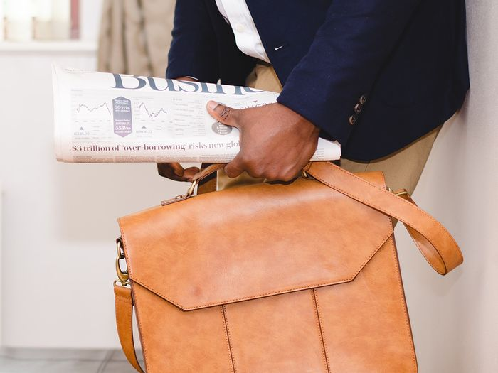 Man with leather bag and business newspaper