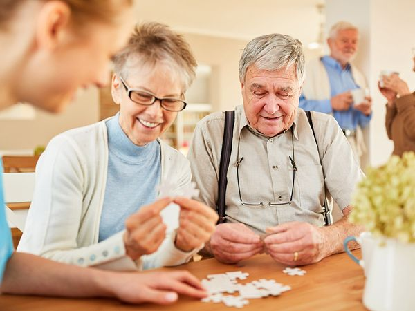 Seniors with Alzheimer's disease or dementia playing puzzles with senior care.