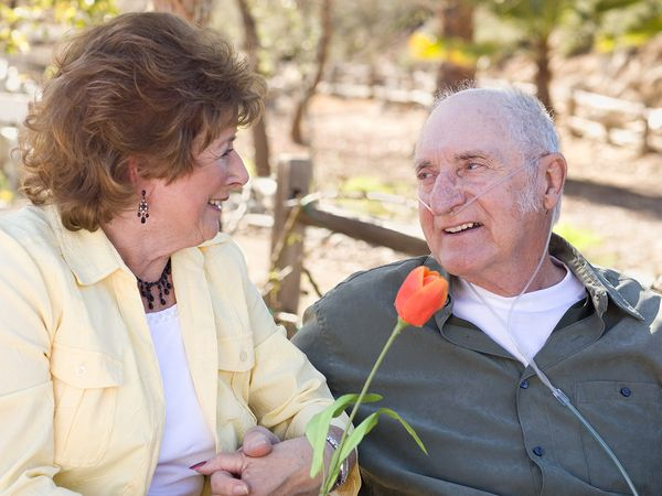 A couple of seniors sitting on a bench holding hands and smiling at each other.