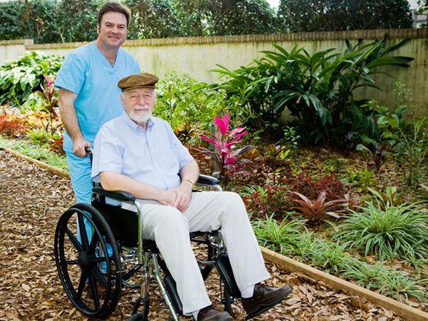 Nursing home orderly takes a senior man for a walk in the garden.