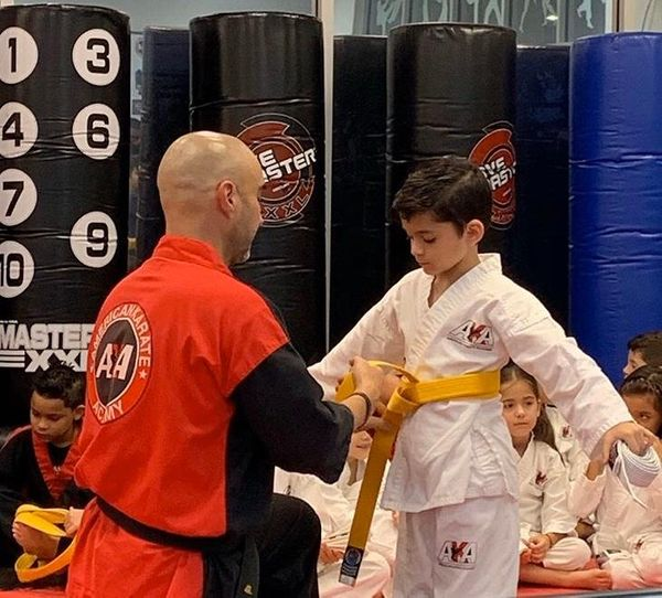 mr. garcia putting yellow belt on sebastian.jpg