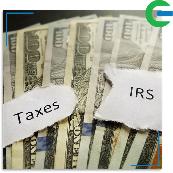 Taxes and IRS paper notes over $100 bills.