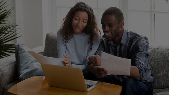 Young Black couple discussing tax information with paperwork and on the computer.