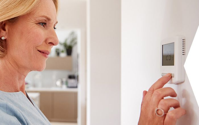 A woman pressing thermostat