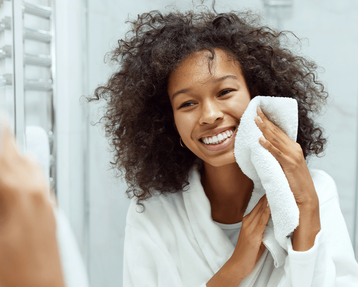 black woman washing her face and smiling
