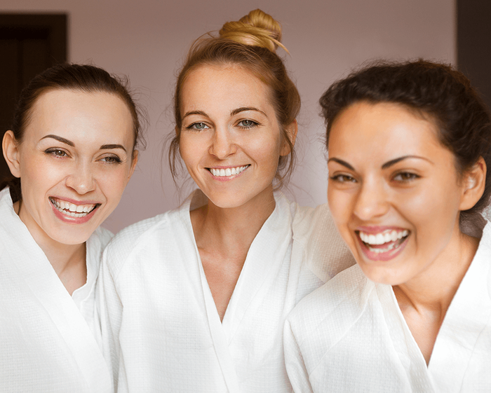 three women in white robes smiling