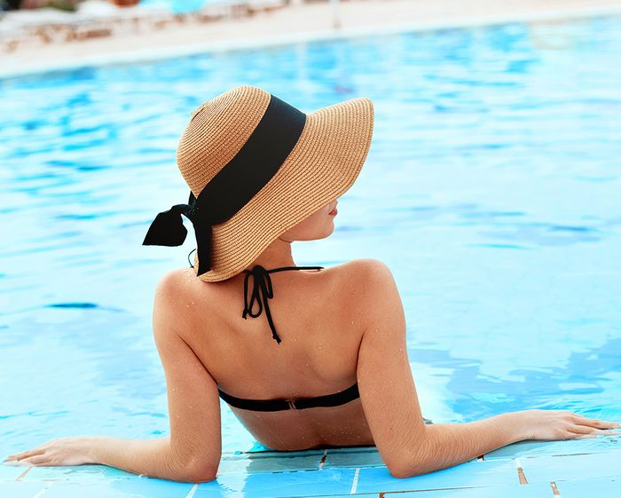 woman in bathing suit leaning against a pool