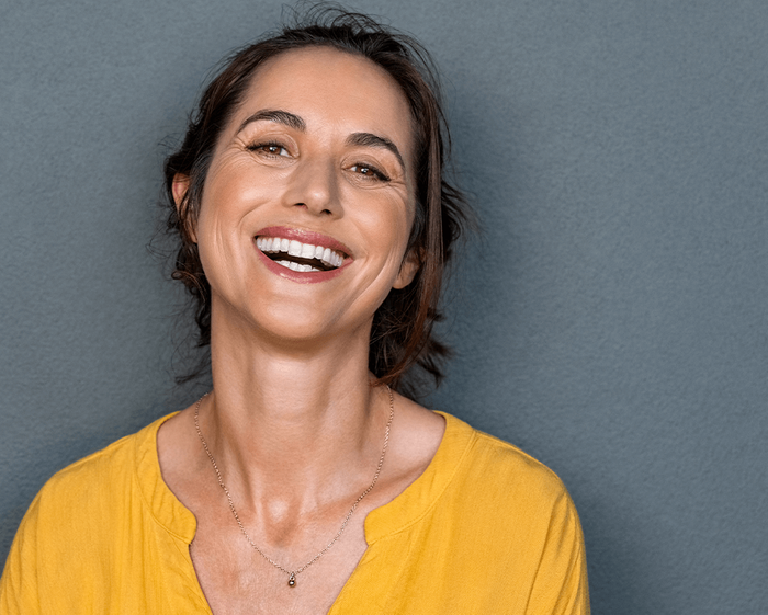 woman smiling and wearing a yellow top