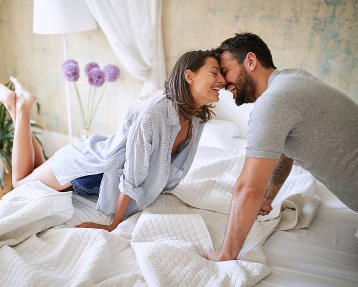 couple kissing/smiling from each side of a bed