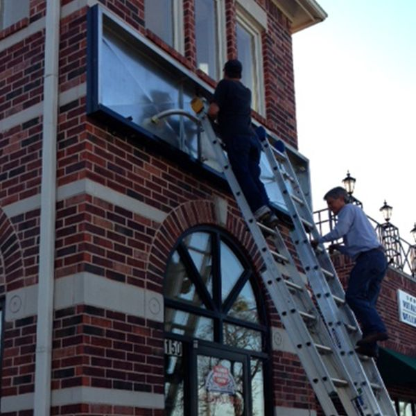 Cabinet sign being installed on the side of a building.