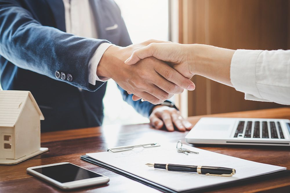 Shaking hands over real estate contract