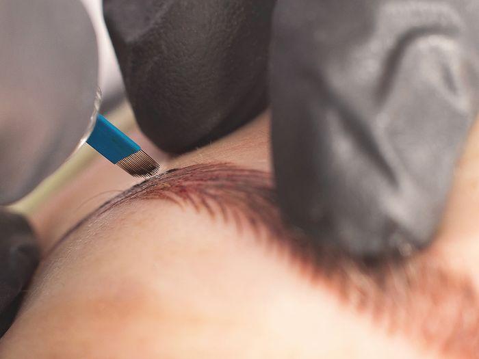 Close-up image of a makeup artist microblading an eyebrow.