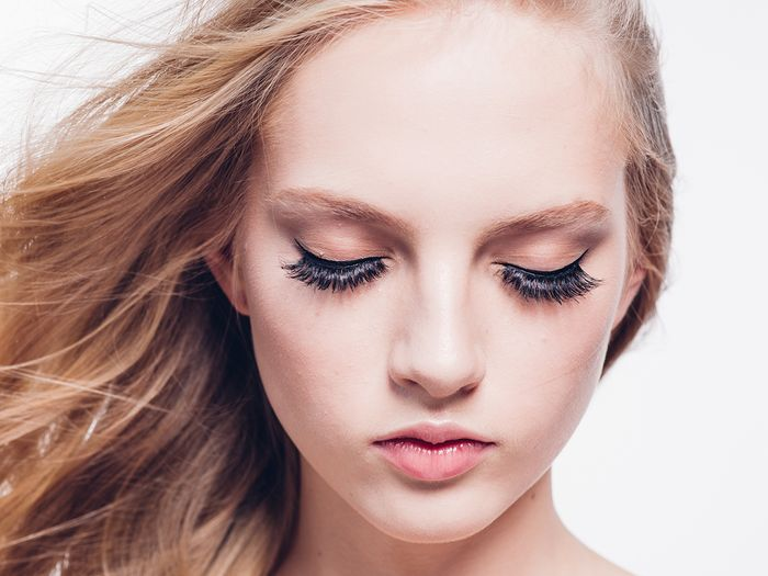 Image of a blonde woman with her eyes closed showing her lash extensions.