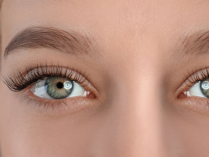 A close up image of a woman with natural-looking healthy eyebrows
