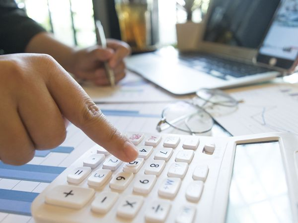Accountant with financial documents spread across desk using a calculator.