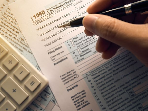 Person filling out a tax form.