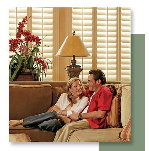 Image of a couple relaxing with plantation shutters on thei window.