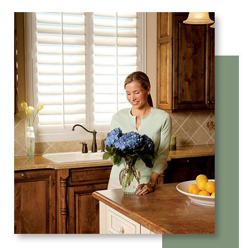 Image of a woman sitting in front of plantation shutters.