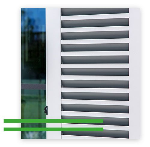 Image of white vinyl shutters on the outside of a window