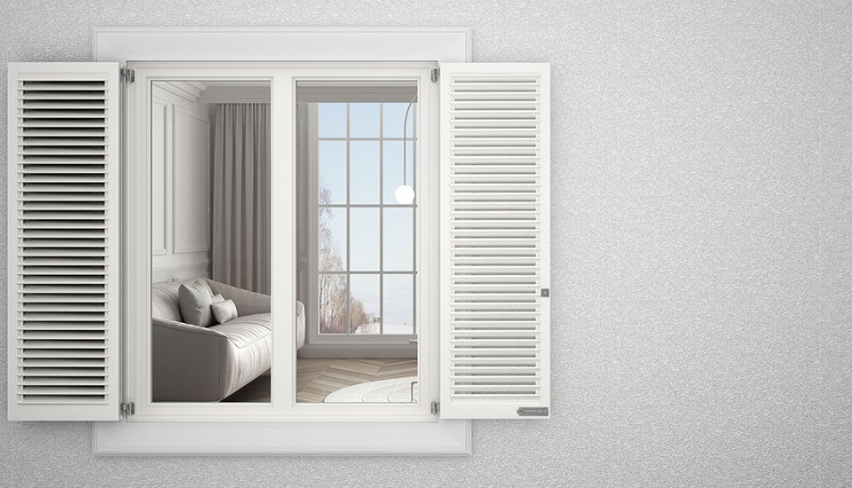 Image of white shutters on the outside of a window on a house with a light grey wall