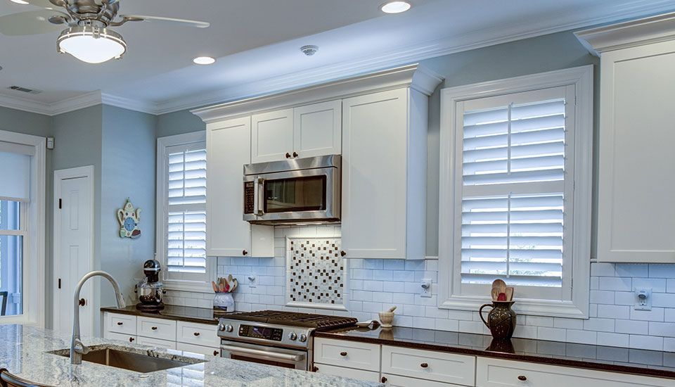 Image of a kitchen with white shutters on the windows above the countertops