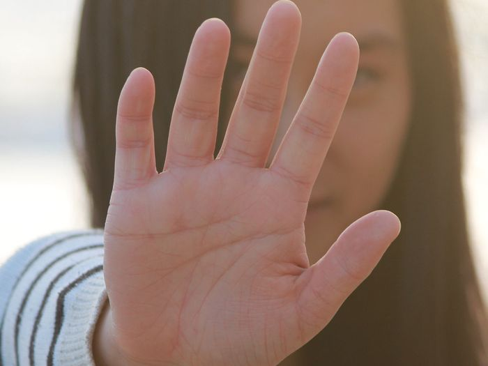 girl holding up a hand to say stop