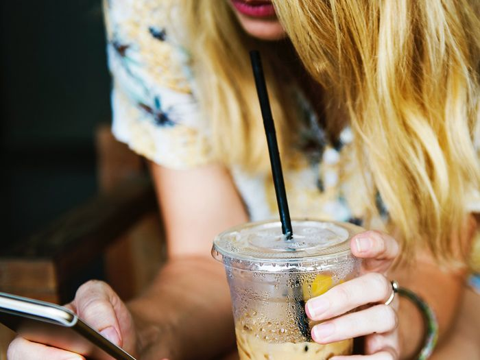Concerned teen using phone and drinking coffee.