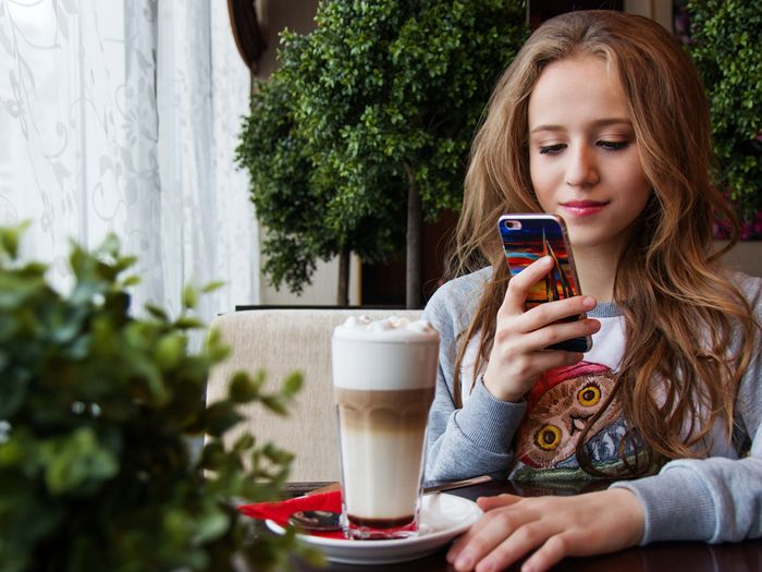 Teen smiling and using a smartphone in a coffee shop.