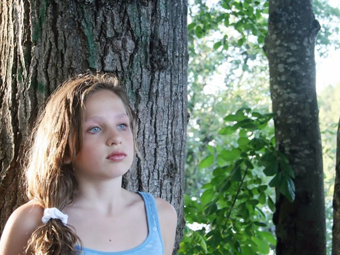 sad young girl leaning against a tree