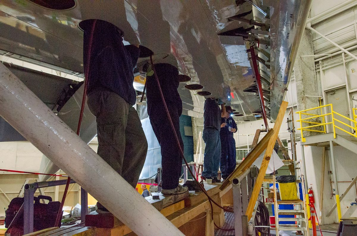 Aviation Techs adjust instruments in the 737 wing to accommodate winglet and scimitar flight surfaces installation