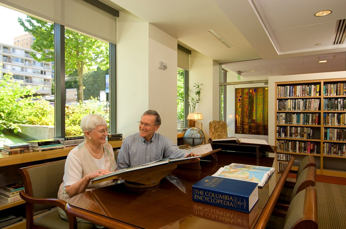 Horizon House couple discusses possible trip while looking at map book in the library.