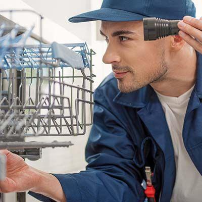 dishwasher repair technician using flashlight to look into dishwasher