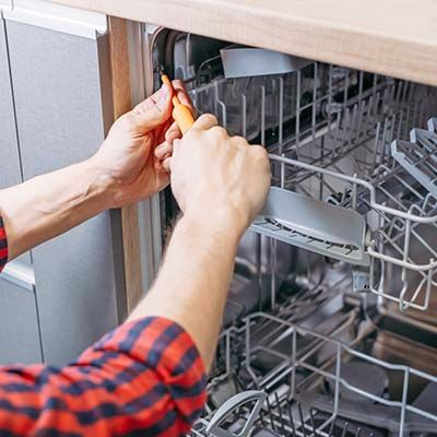 repair technician using screwdriver on dishwasher
