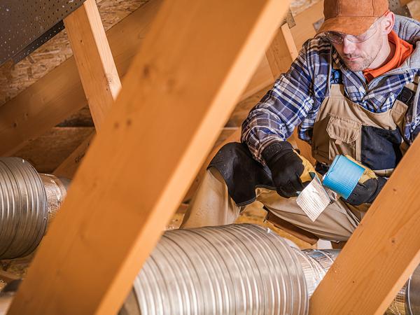 HVAC technician charging a heat pump with refrigerant readers.