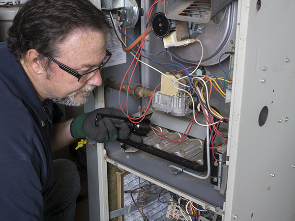 HVAC technician looking over a gas furnace with a flashlight.