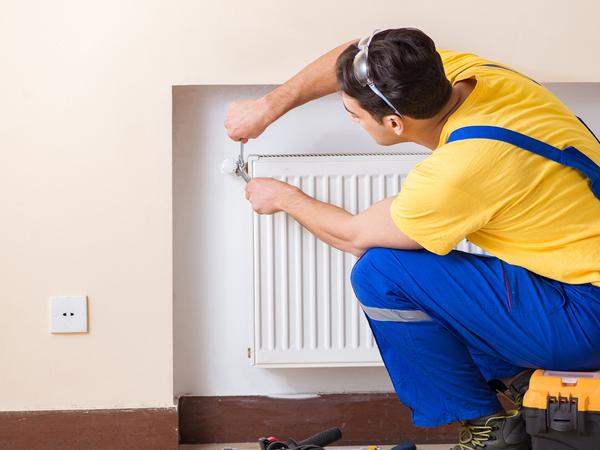 Young repairman contractor repairing heating panel.