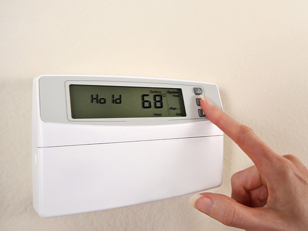 """Woman's hand adjusts thermostat set at 68, display reads """"Hold."""""""