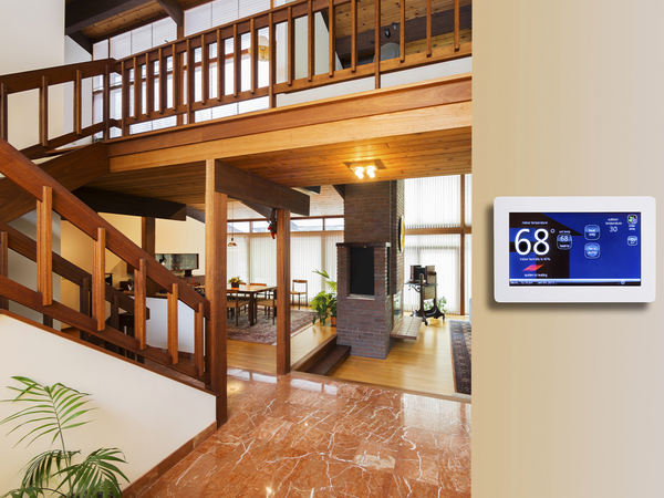 Programmable electronic thermostat on beige wall in house entrance way.