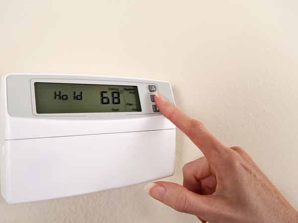 Adjusting and setting thermostat to save energy.