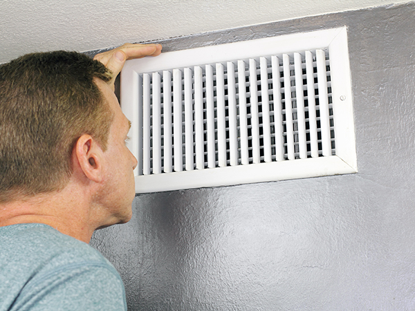 Man looks at his home's air duct vent.