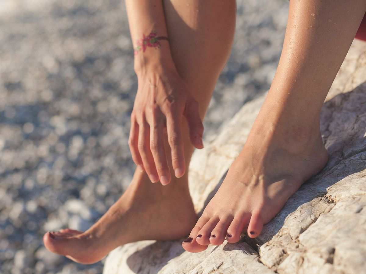 Person reaching for their feet while sitting on a rock at the beach