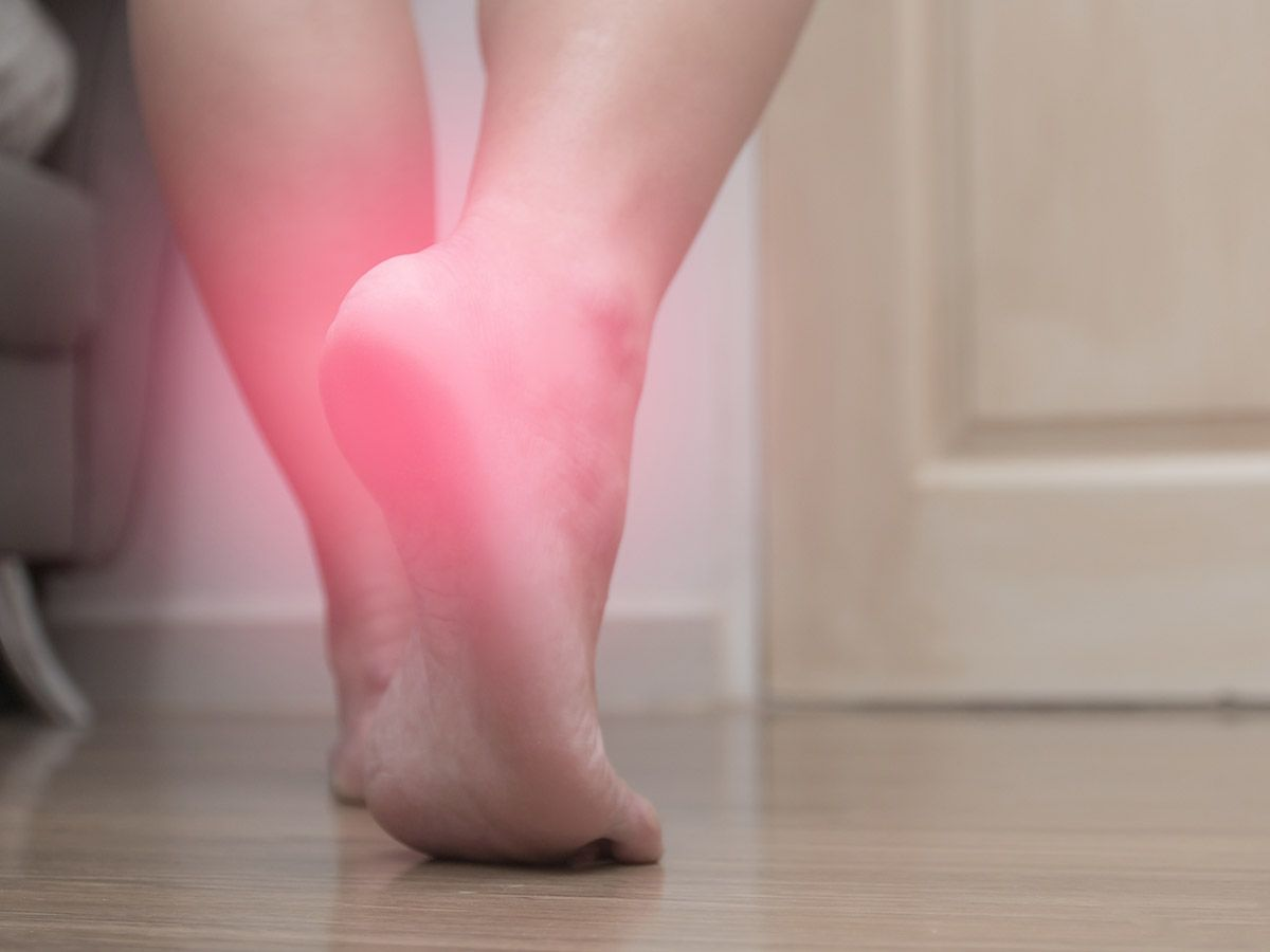 Person walking with red radiating pain occurring in the heel of their back foot