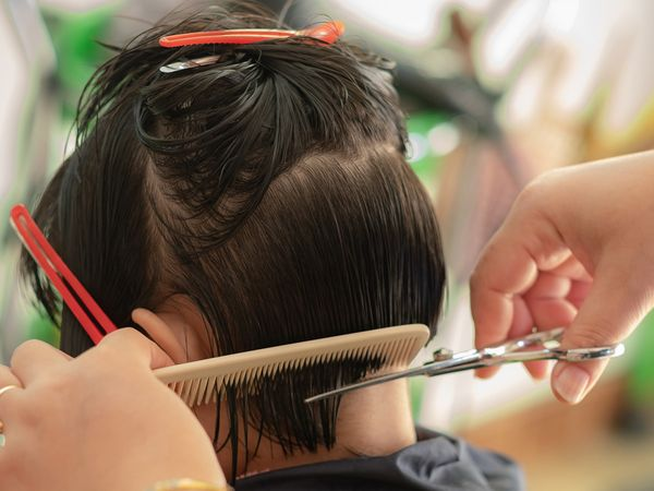 Back side of a girl getting her hair cut in a hair salon.