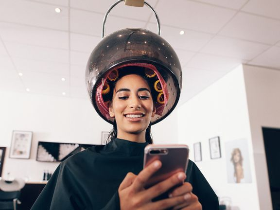 A woman smiles at her phone while she sits underneath a large hairdryer.
