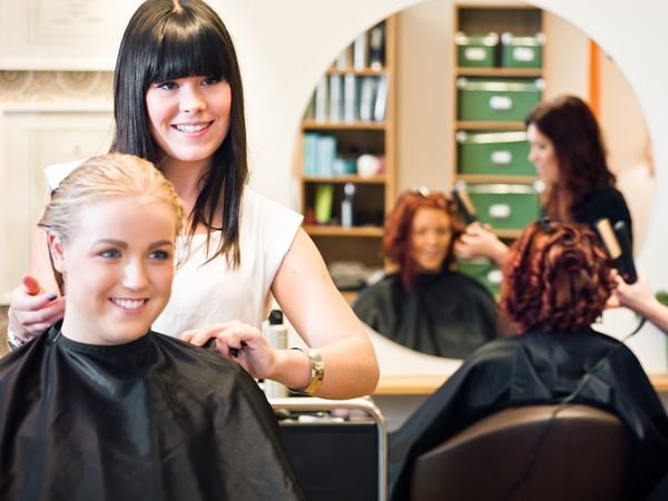 A hair stylist and customer sit in a salon chair smiling into a mirror with another hairdresser and client blurred in the background