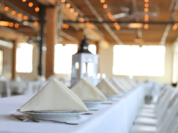 White seats and dressed tables for a large event dinner in an enclosed event space
