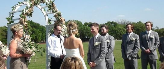 Officiant and couple getting married with flowering arch behind them