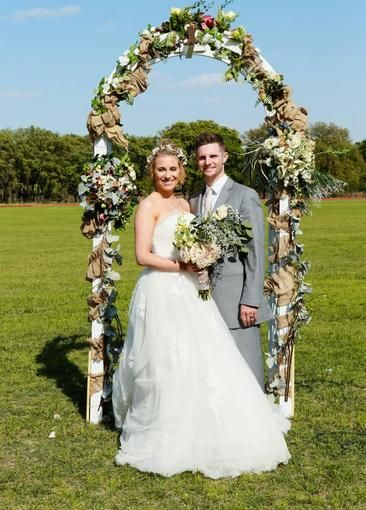 Couple posing in front of flowering arch on wedding day