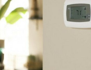 Air conditioning thermostat mounted on wall displaying seventy one degrees.jpg