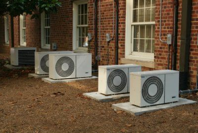Five air conditioning units outside of red brick building.jpg